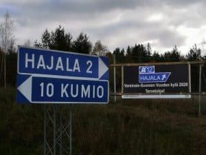 Vuoden kylä -kyltti moottoritien kupeessa