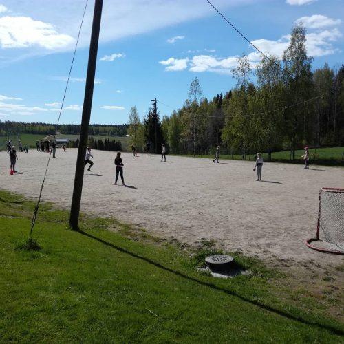 Pesäpalloa koulun kentällä