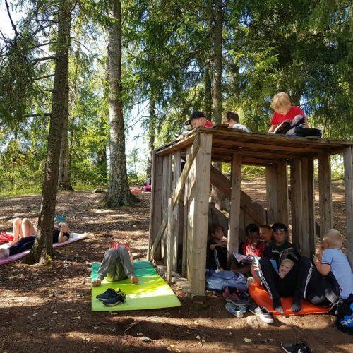 Lapset leikkivät ja opiskelevat rakentamissaan majoissa